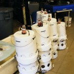 SMCC-built bucket drifters stacked in the lab. The buckets float upside-down with only an inch or two above the waterline.