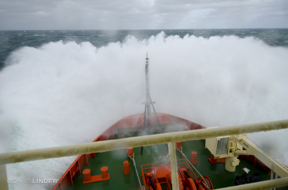 A large wave crashes over the bow of the Palmer.